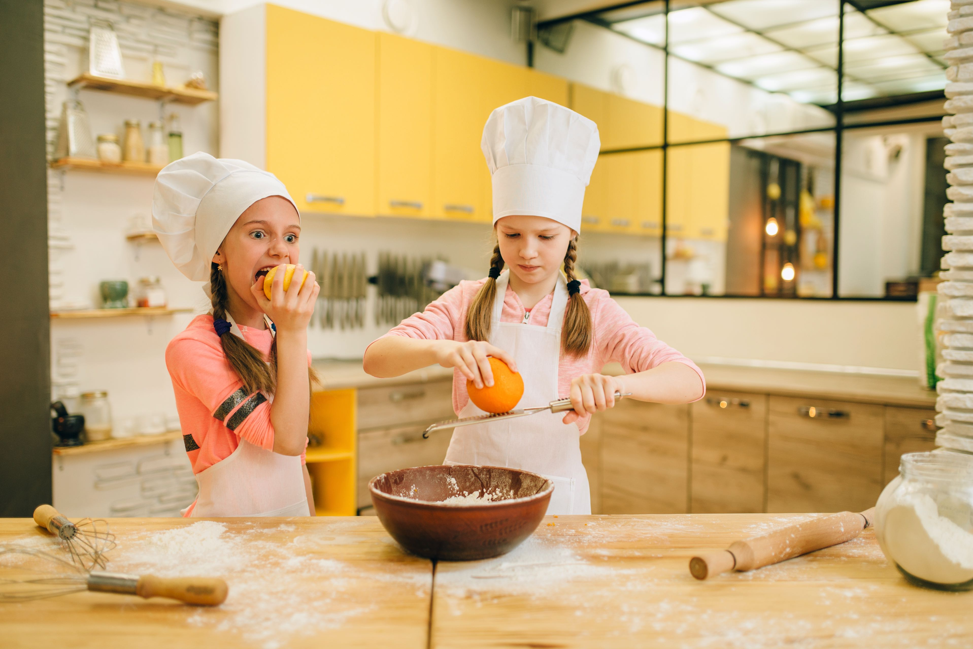 Little girls cooks in caps rubs orange to the bowl