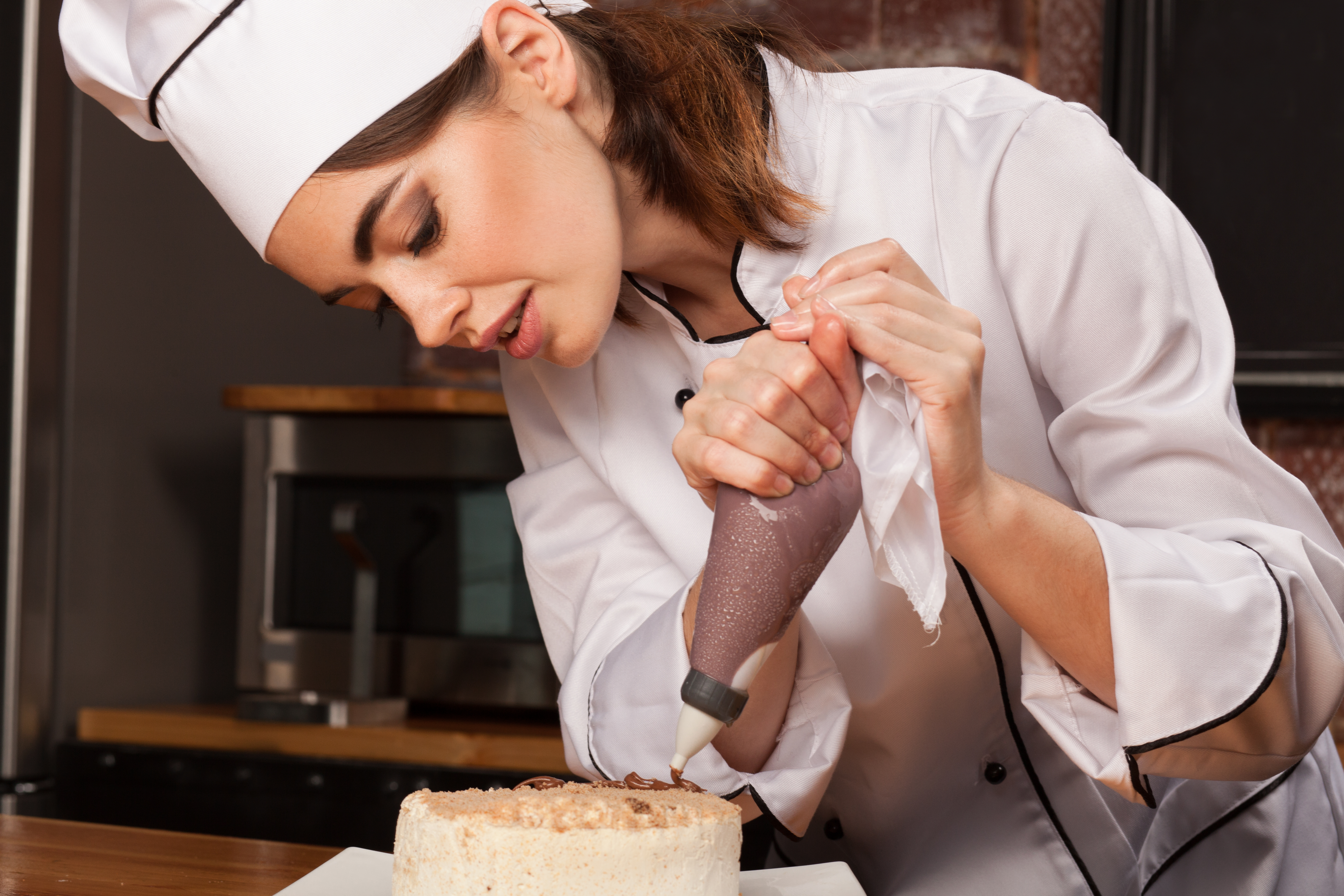 Female chef cook preparing a sweet cake in the kitchen